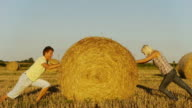 HD: Couple Pushing Hay Bale Against Each Other video