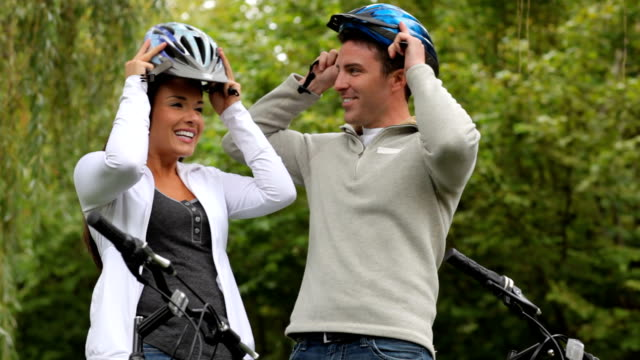 Couple putting on bicycle helmets video