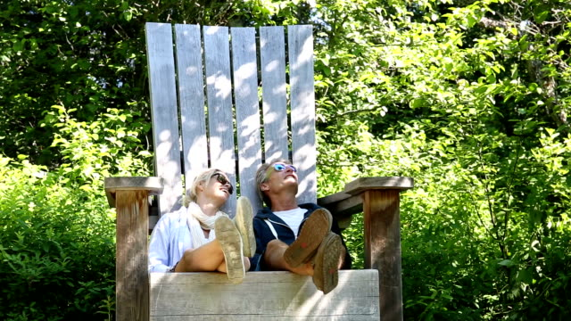 Couple relax in huge wooden chair, in forest video