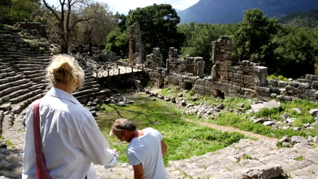 Couple relax on stone steps of ancient Greek amplitheatre video
