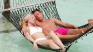 Couple Relaxing In Beach Hammock video