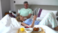 Couple Relaxing In Bed With Newspaper And Digital Tablet video