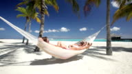 couple relaxing in hammock on tropical beach video