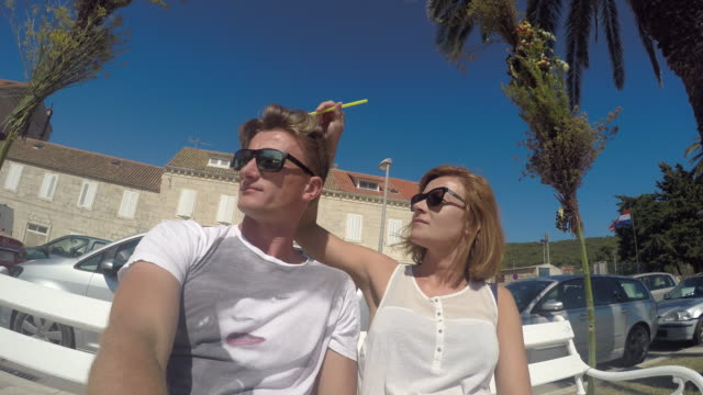 WS Couple relaxing on a bench in coastal town video