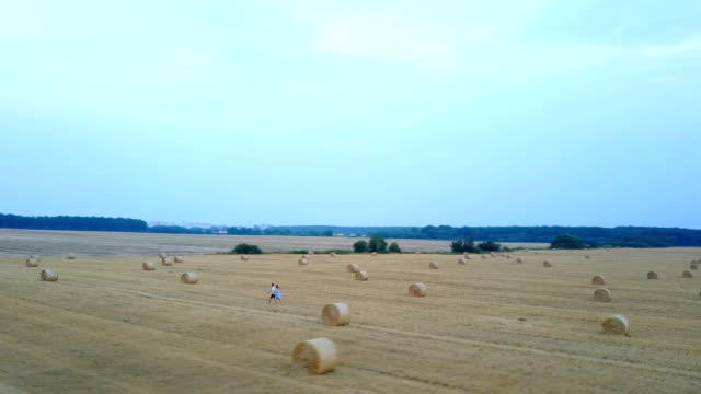Couple Relaxing On A Field With Hay Bales video