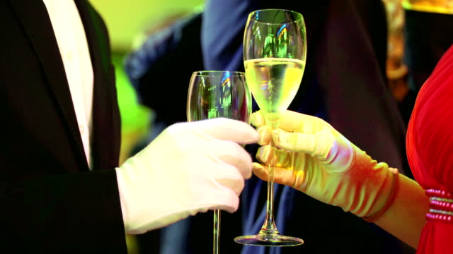 Couple rest after waltz and other Historical ballroom dances. Champagne glass with bubbles close up video
