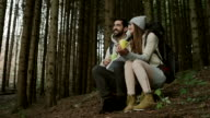 Couple resting in the forest and drinking coffee video
