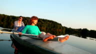 Couple resting on boat after paddling, beautiful nature, sunset video