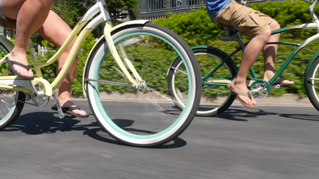Couple riding bicycles together, closeup video