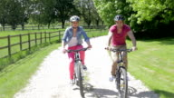 Couple Riding Mountain Bikes Along Country Track video