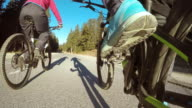 POV Biker pedaling alongside his friend in countryside video