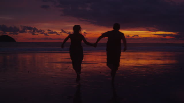 Couple run out to ocean at sunset video