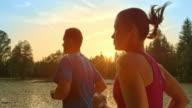 SLO MO TS Couple running along lake at sunset video