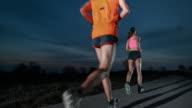 SLO MO Couple running along the road at dusk video