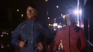 SLO MO Couple running in the city at night video