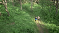 AERIAL Man and woman running on path through forest video