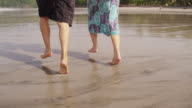 Couple running on beach, closeup of feet, slow motion. video