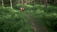 AERIAL Couple running on forest trail in sunshine video
