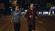 SLO MO TS Couple running the city streets at night video