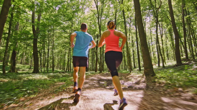 SLO MO TS Couple running through the forest video
