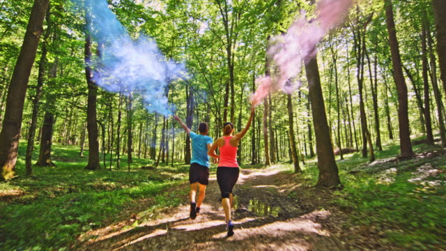 SLO MO TS Couple running through the forest with blue and red smoke flares video