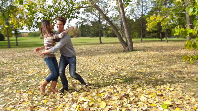 Couple runs and jumps into pile of leaves video