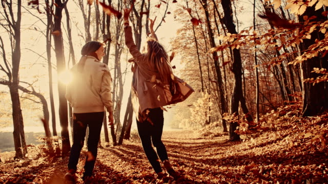 SLO MO Couple scattering leaves while running in the forest video