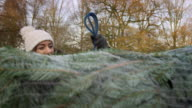 Couple Securing Christmas Tree Onto Roof Of Car video