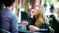 Couple share a latte at sidewalk cafe video