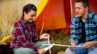 Couple sharpening wood sticks on camping for sausage and marshmallow video