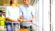 Couple shopping in supermarket. video