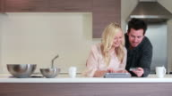couple shopping online in kitchen video