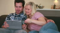 couple shopping online on sofa video