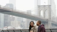 A couple sits on a bench and talks while in front of the Brooklyn Bridge video