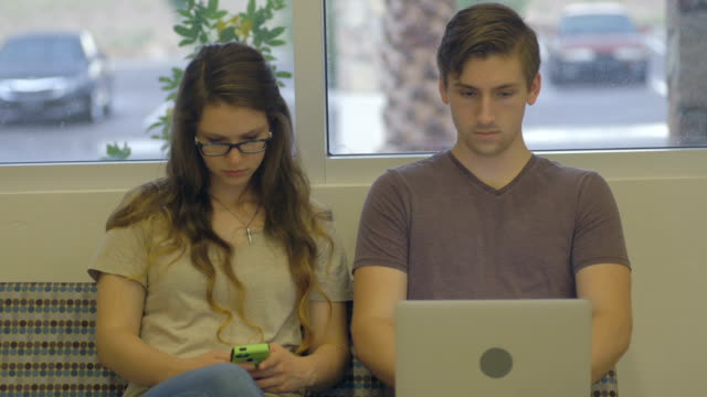 Couple Sits Waiting and Looking at Their Devices video