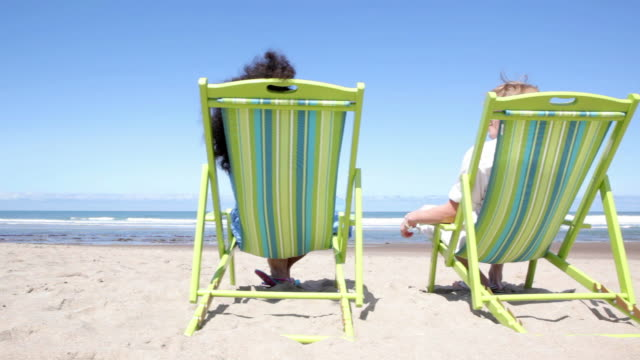 Couple sitting in chairs at beach video