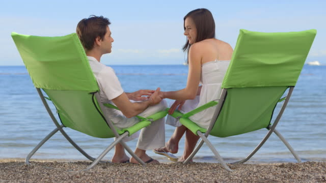 HD: Couple Sitting In Chairs At Beach video