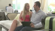 Couple Sitting In Hotel Lobby Looking At Digital Tablet video