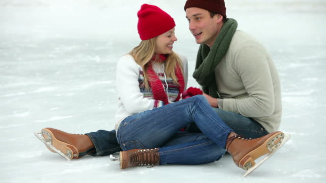 Couple sitting in ice skating rink together video