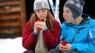 Couple sitting in snow together having hot cocoa video