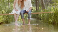 SLO MO Couple sitting on a footbridge with their feet in the brook video