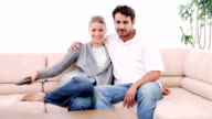 Couple sitting on a sofa while watching movie video