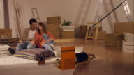 Couple sitting on floor in new apartment video