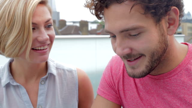 Couple Sitting On Roof Terrace Using Digital Tablet video