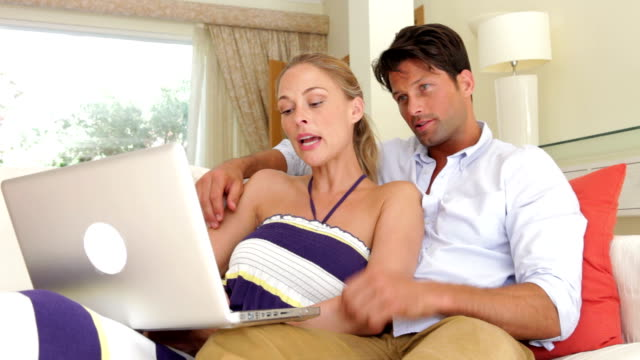 Couple Sitting On Sofa Using Laptop Computer video