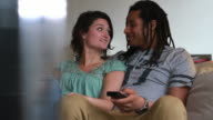 Couple sitting on sofa watching Television video