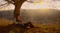 Couple sitting under the tree at sunset video