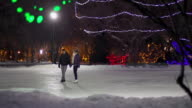 Couple skates together on a snowy winter evening. video