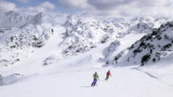 AERIAL Couple skiing down the slope on sunny day video