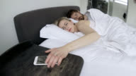 Couple sleeping when alarm from the smartphone goes on video